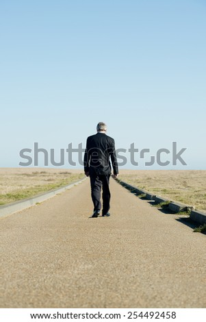 Businessman Walking Away Down Long Road - stock photo