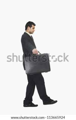 Businessman walking carefully with a briefcase - stock photo