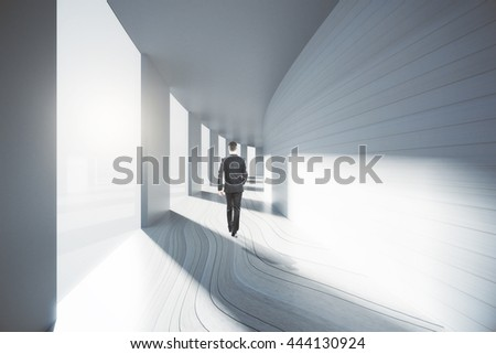 Businessman walking down bright empty corridor interior with sunlight. 3D Rendering