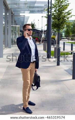 Businessman walking down the street with a briefcase, talking on a cell phone