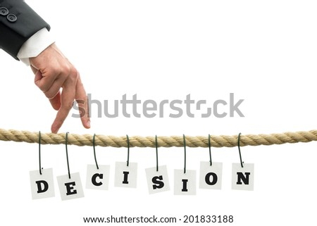 Businessman walking his fingers along a frayed rope with sign Decision hanging off it. - stock photo