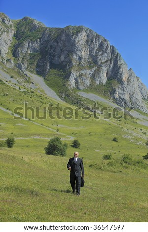 Businessman walking in a mountaineous area.