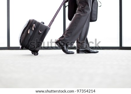 businessman walking in airport with his luggage - stock photo