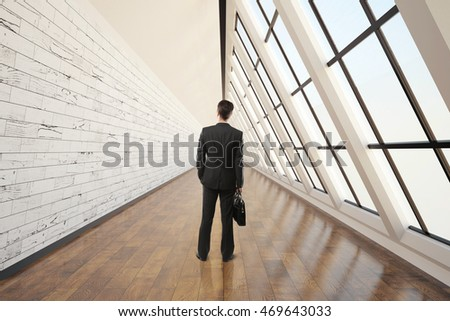 Businessman walking in clean corridor interior with dark wooden floor, light wall, concrete ceiling and panoramic window. 3D Rendering