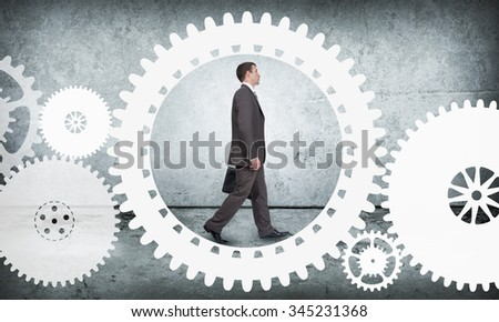 Businessman walking in cog wheel on abstract background