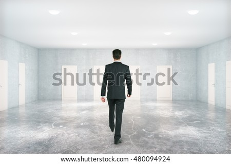 Businessman walking in concrete room with many white doors. Success concept. 3D Rendering