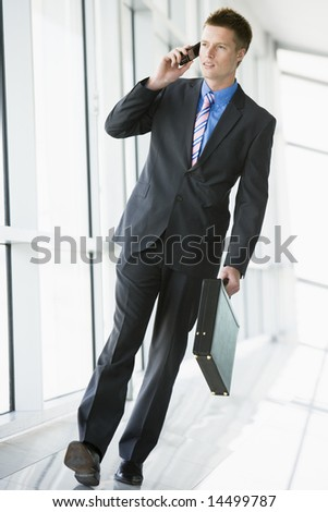 Businessman walking in corridor using cellular phone - stock photo