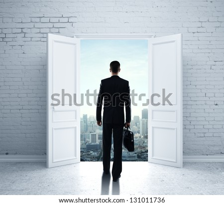 businessman walking in open door to city