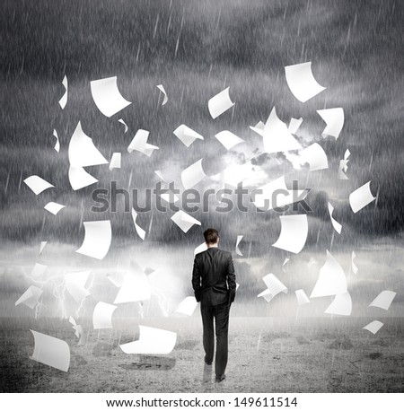 businessman walking in rainy weather with flying around paper