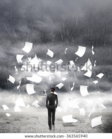 businessman walking in rainy weather with flying around paper - stock photo