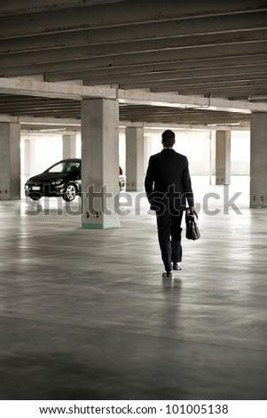 Businessman walking in underground parking - stock photo