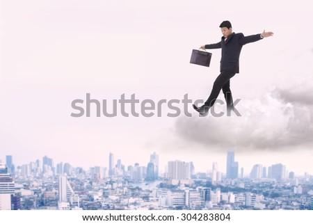Businessman walking on a cloud near miss. - stock photo