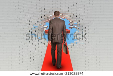 Businessman walking on arrow pierced brick wall - stock photo