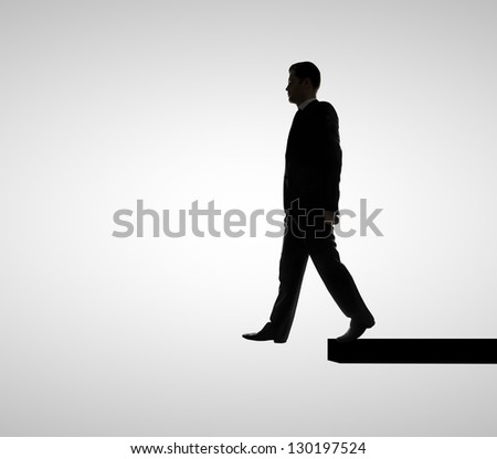 businessman walking on edge  on white background - stock photo