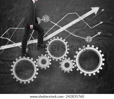 businessman walking on gears and drawing chart on wall - stock photo