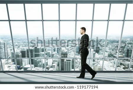 businessman walking on office and city in window