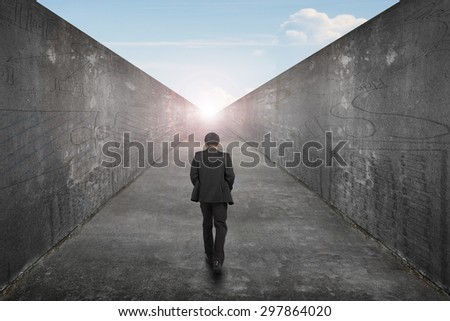 Businessman walking on one way road toward the exit of sun sky view, with high dirty concrete wall background. - stock photo