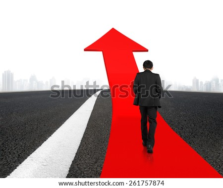 Businessman walking on red arrow up road with asphalt pavement and cityscape background - stock photo
