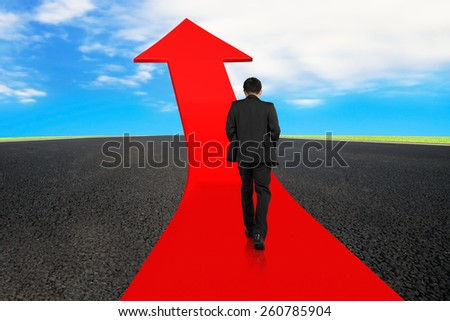 Businessman walking on red arrow up road with asphalt pavement and sky clouds background - stock photo
