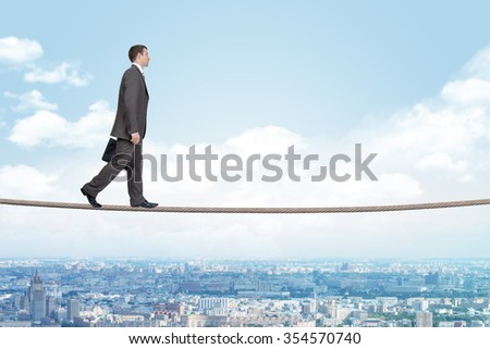 Businessman walking on rope above city with closed eyes