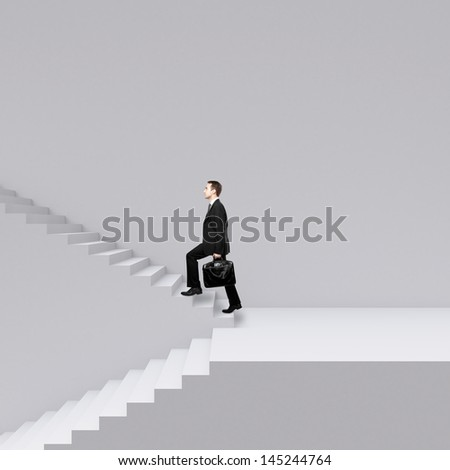 businessman walking on stairs on a gray background - stock photo