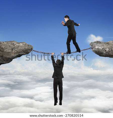 Businessman walking on the broken rusty iron chains another man holding connect two cliffs with sky cloudscape background, business teamwork concept. - stock photo