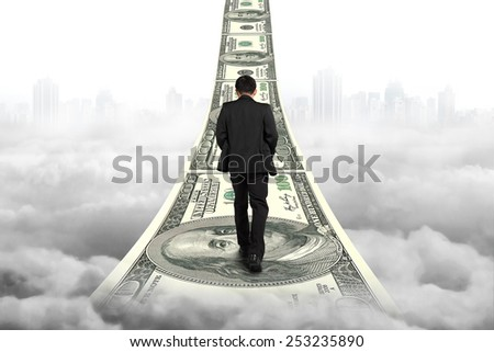 Businessman walking on the money stairs with gray cityscape cloudscape background - stock photo