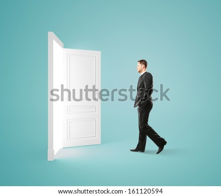 businessman walking to opened door - stock photo