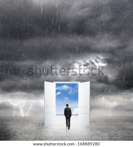 businessman walking to opened door from bad weather to white - stock photo