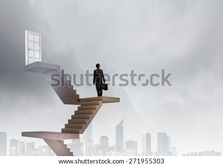 Businessman walking up staircase to door in sky
