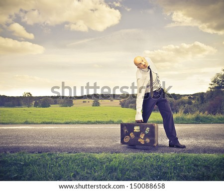 businessman walking with heavy suitcase - stock photo