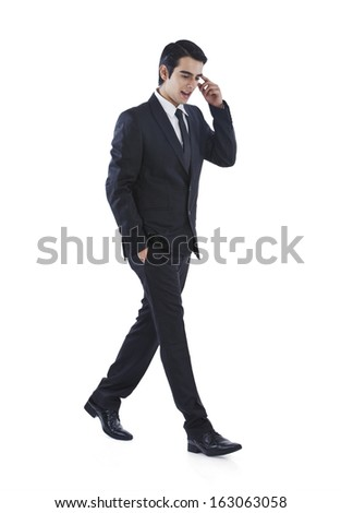 Businessman walking with his hands in pockets and thinking - stock photo