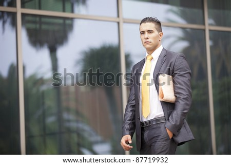 Businessman walking with his newspaper next to his office building - stock photo