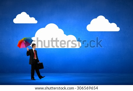 Businessman walking with suitcase and with colorful umbrella