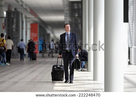 businessman walking with trolley through the crowd on a business trip - stock photo