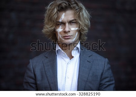 Businessman warrior. Young man makes war paint on his face, concept - stock photo