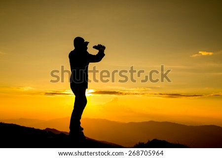 Businessman watch binoculars for his vision  for his vision on the high mountain  - stock photo