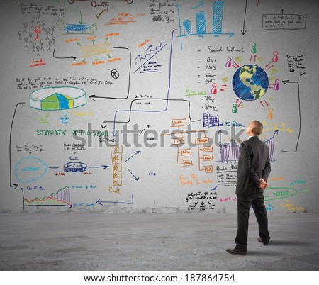 Businessman watching a wall with new business project - stock photo