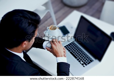 Businessman watching the time in his wear watches,brunette businessman checking the time on his wrist watch, executive looking at the time on his wrist watch, man sitting at table  at business meeting - stock photo