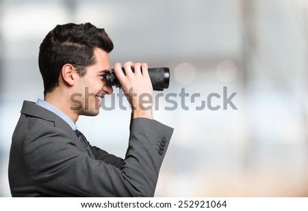 Businessman watching through binoculars - stock photo