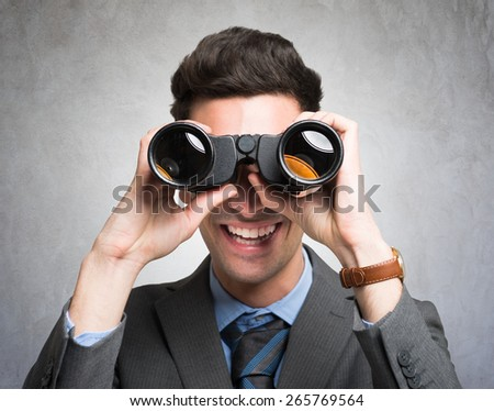 Businessman watching through binoculars in search of new opportunities - stock photo