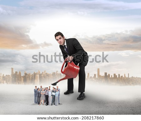 Businessman watering tiny business team against large city on the horizon - stock photo