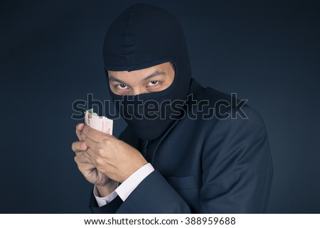 Businessman Wearing a Balaclava Thinking Corruption Plan and Showing the Money