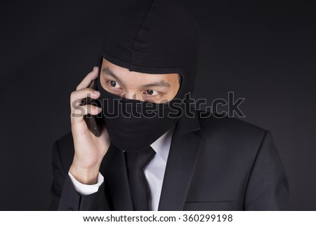 Businessman Wearing a Balaclava Thinking Corruption Plan and Talking Smart Phone