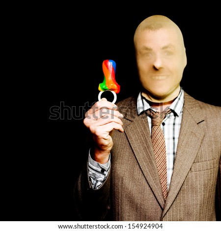 Businessman wearing a stocking mask over his head holds up a colourful striped candy babys dummy while grinning at the ease with which he stole it, conceptual of the idiom Stealing Candy From A Baby - stock photo