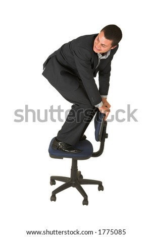 Businessman wearing a suit and a grey shirt.  Making a stunt on an office chair.