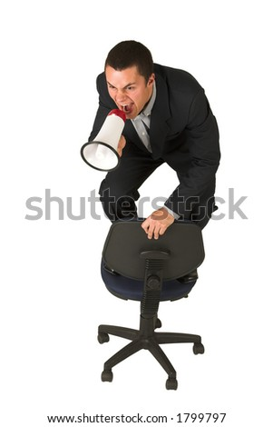 Businessman wearing a suit and a grey shirt.  Making a stunt on an office chair with a megaphone in his hand.