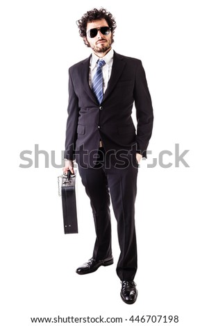 Businessman wearing a suit with a secure suitcase attached with handcuffs isolated over a white background