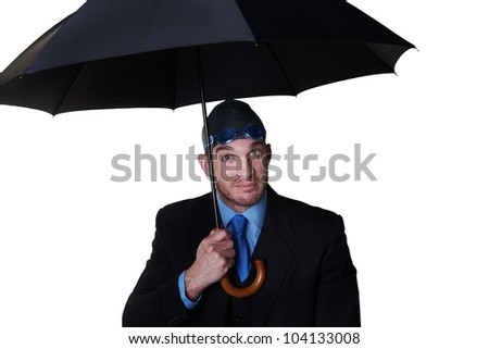 businessman wearing a swimming cap, goggle and holding up a umbrella