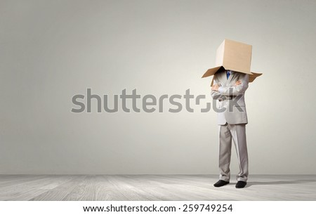 Businessman wearing carton box with drawn emotions on head - stock photo